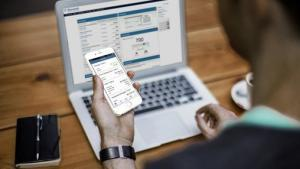 onlinebanking-man-using-mobile-app-and-laptop